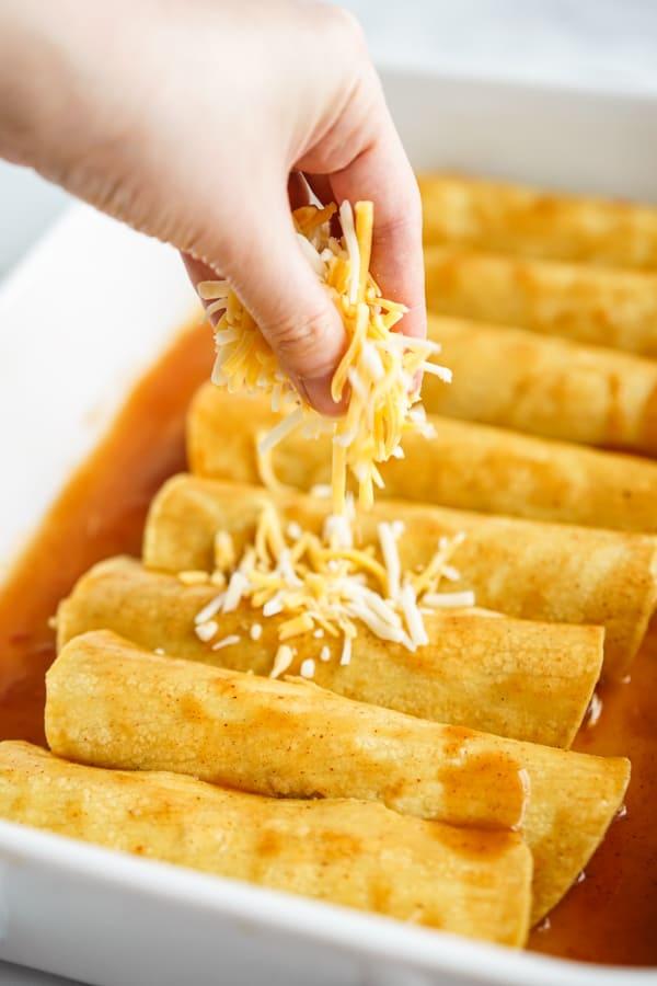 Adding shredded cheese to enchiladas