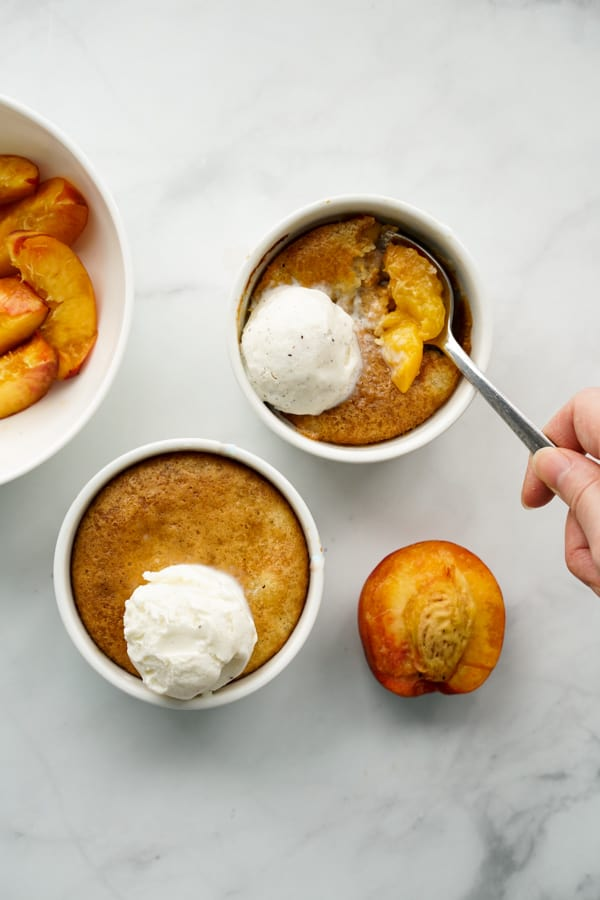 Two ramekins of peach cobbler with ice cream on top, a spoon digging into one of them