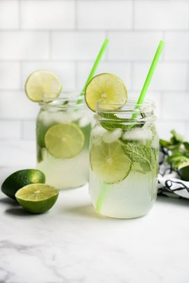 Two mason jar glasses of sparkling lime juice with lime