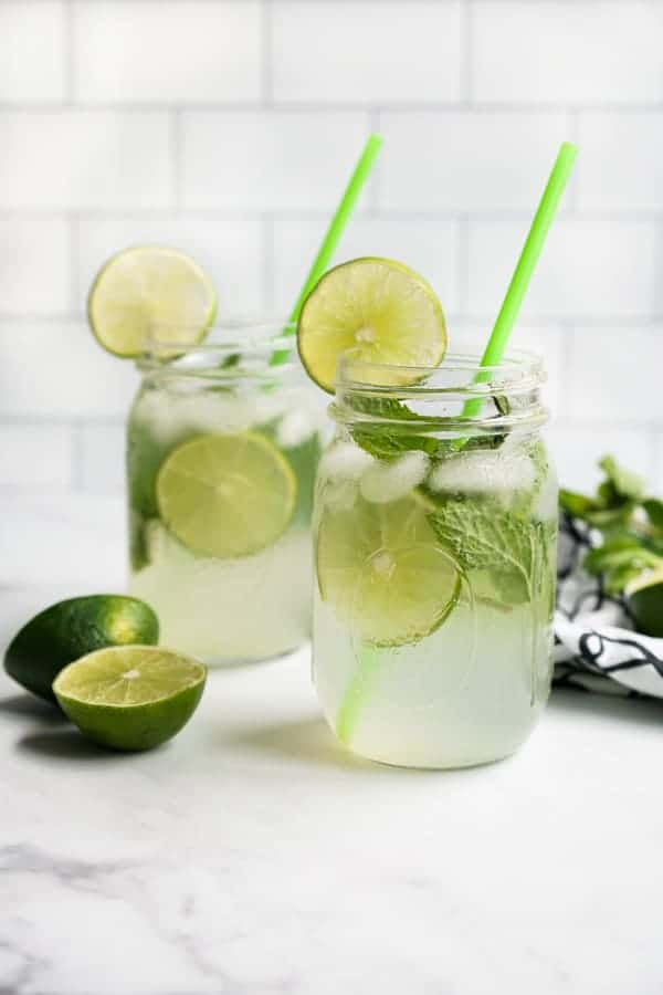 Two mason jars of mojito mocktails filled with lime and mint leaves, with slices of lime next to them.
