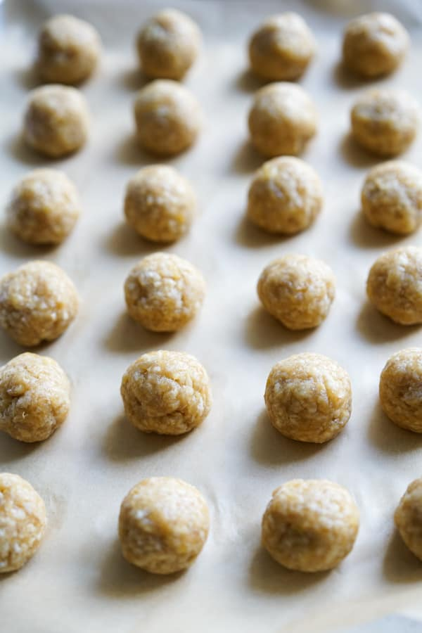 Uncooked chicken meatballs lined on a tray