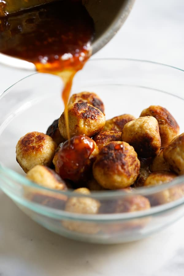 Pouring sweet and sour sauce onto chicken meatballs