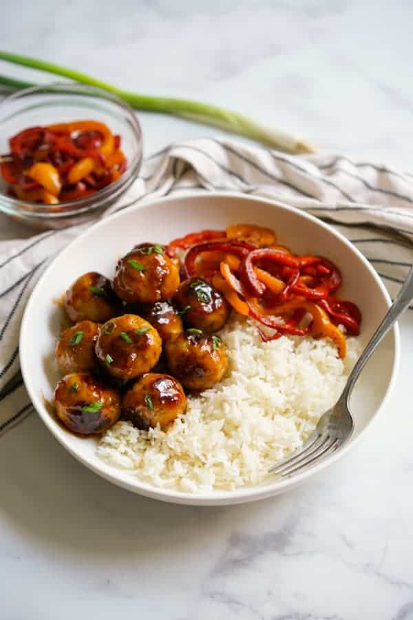 A bowl of sweet and sour meatballs, rice and bell peppers, with a fork in the bowl