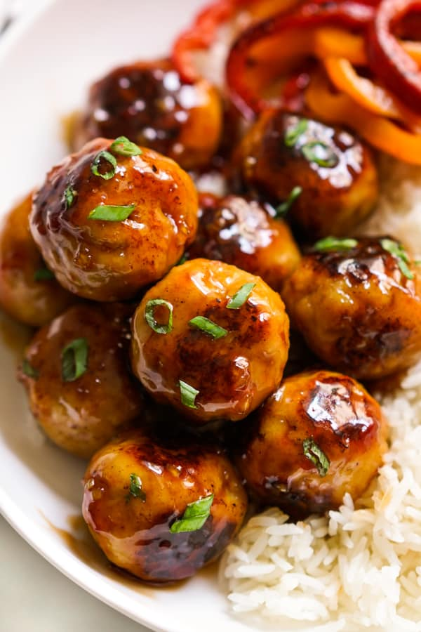 Closeup of chicken mealballs coated with sticky sweet and sour sauce