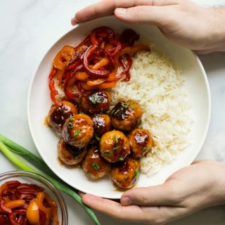 Two hands holding a bowl of sweet and sour meatballs, rice and bell peppers