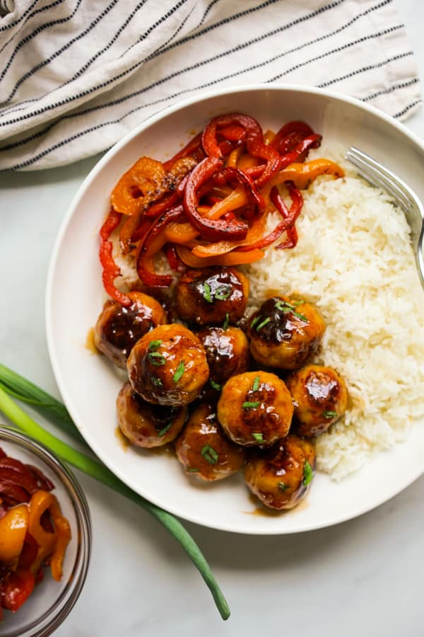 A bowl of chicken meatballs coated in sweet and sour sauce, rice and bell peppers