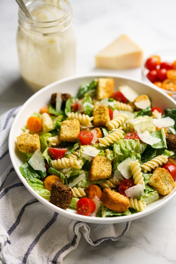 A bowl of Caesar salad with pasta, tomatoes and croutons. Caesar dressing in the background