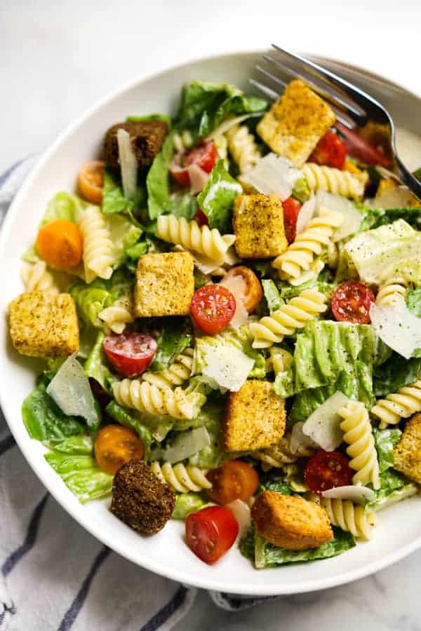 Closeup of a bowl filled with lettuce, rotini pasta, tomatoes, parmesan and croutons
