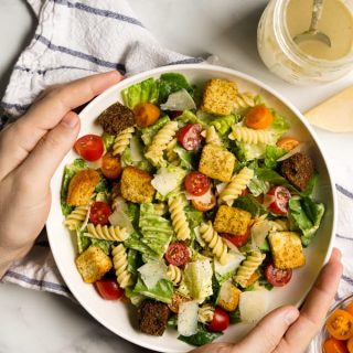 Hands holding a bowl of Caesar Pasta Salad with a mason jar of dressing on the side