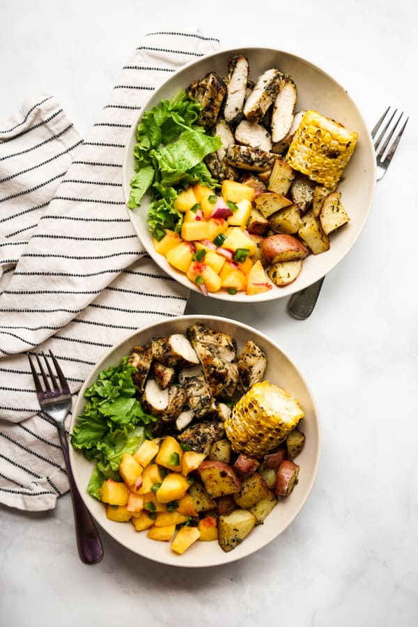 Two bowls of grilled chicken, grilled potatoes, corn on the cob, lettuce and peach salsa, with forks next to each bowl