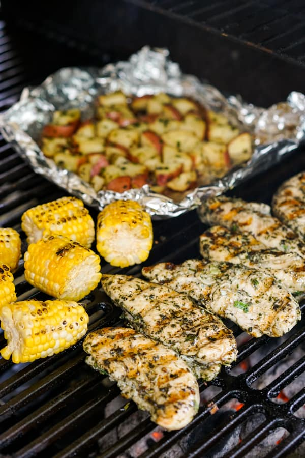 Grilled chicken tenderloins and grilled corn placed directly on the charcoal grill while cubed red potatoes are placed on a foil on the grill