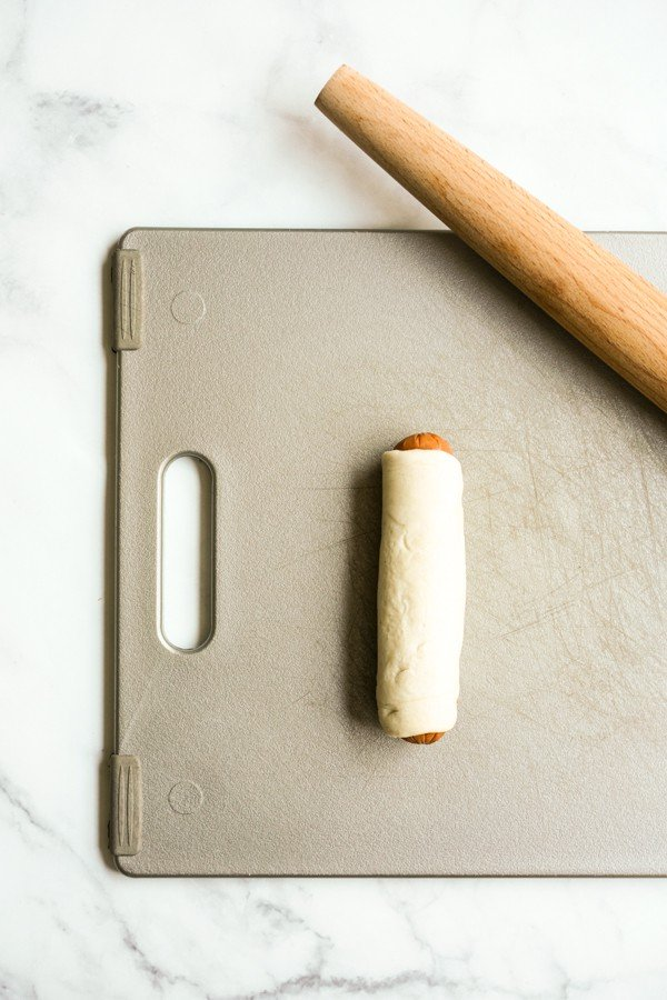 sausage rolled in dough on cutting board