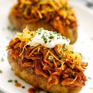 Two baked russet potatoes topped with shredded BBQ chicken, shredded cheddar cheese, sour cream, and chives