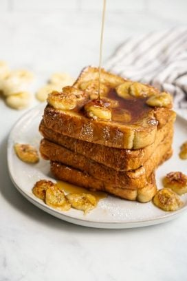 Drizzling maple syrup onto a stack of french toast