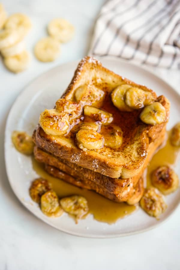 A stack of french toast topped with caramelized bananas and maple syrup