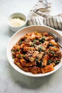 A bowl of rigatoni pasta coated in creamy tomato sauce, combined with Italian sausage and spinach