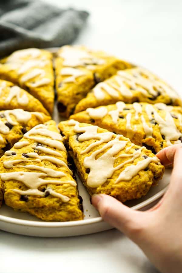 Hand grabbing a slice of triangular pumpkin scone with chocolate chips.