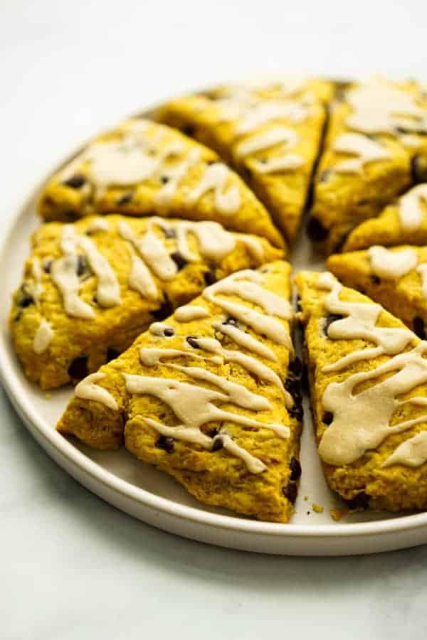 A plate of triangular pumpkin chocolate chip scones.