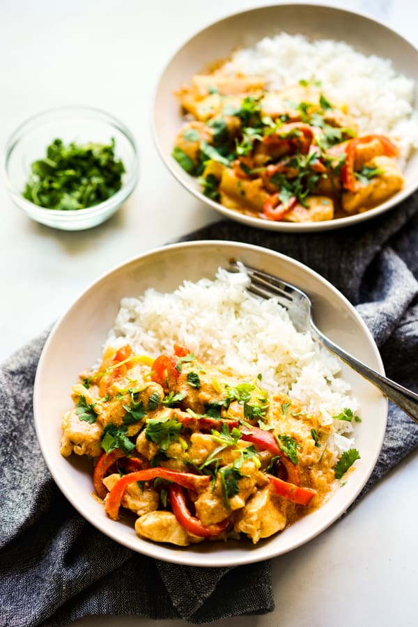 Two bowls of rice topped with Thai Red Curry with Chicken