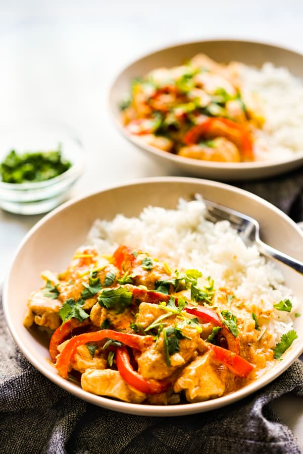 A bowl of rice with chicken curry, bell peppers and zucchini
