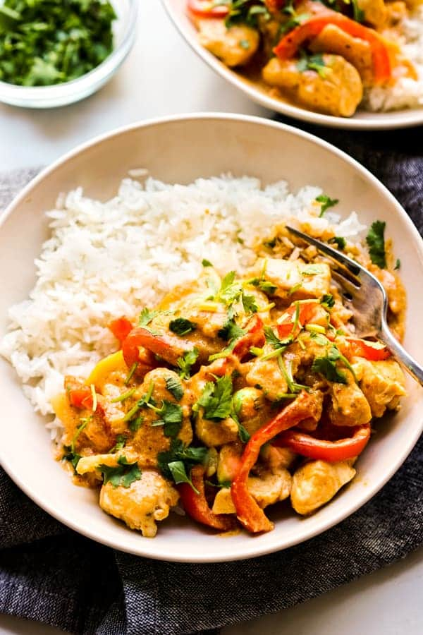 Close up of a bowl of rice topped with Thai curry with chicken, bell peppers and zucchini.