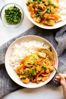 Two bowls of Thai Red Curry with Chicken on rice, with a fork digging into one of them