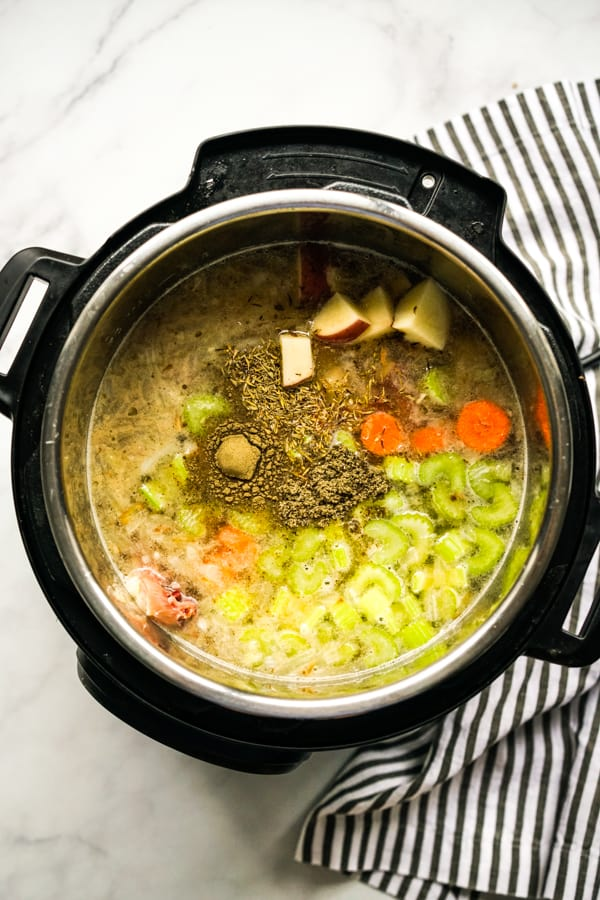 Chicken broth, chicken, carrots, celery and herbs in the Instant Pot