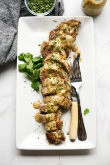 Sliced pork tenderloin on a rectangular plate topped with cream gravy