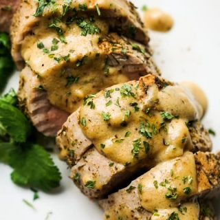 Close up of roasted pork tenderloins topped with gravy and chopped parsley