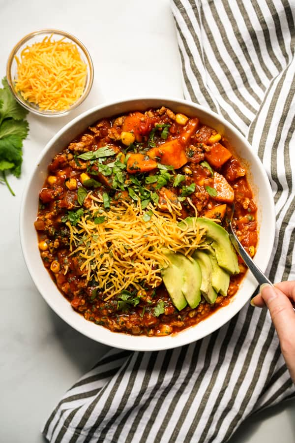 Top down view of a bowl of chili filled with sweet potatoes, turkey, avocados, cilantro and cheese