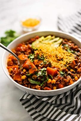Spoon digging into a bowl of Turkey Sweet Potato Chili with garnishes