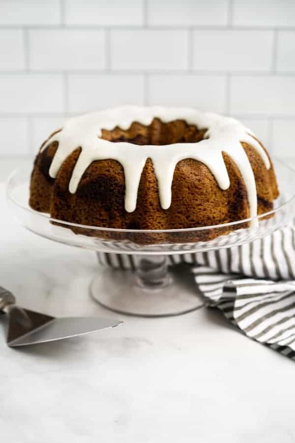 Cinnamon swirl bundt cake drizzled with icing on a cake stand