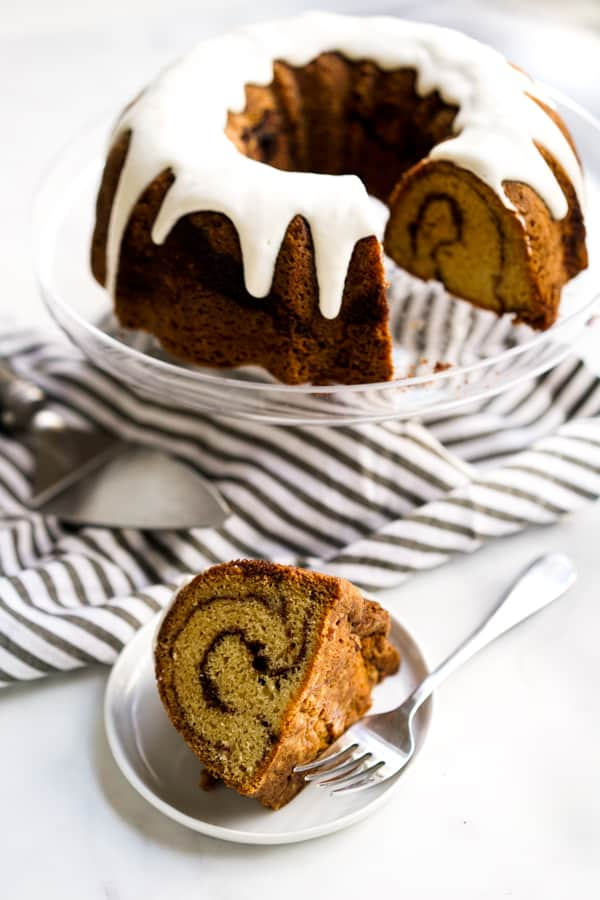 A slice of Cinnamon Bundt Cake with the whole cake in the background