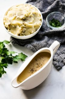 Gravy boat filled with homemade gravy with mashed potatoes and fresh parsley in the background