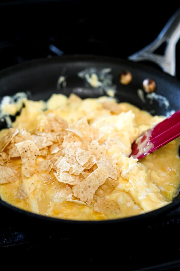 Adding tortilla chips to scrambled eggs in a skillet
