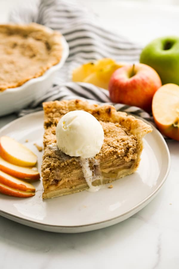 A slice of apple crumble pie topped with vanilla ice cream with a whole pie in the background