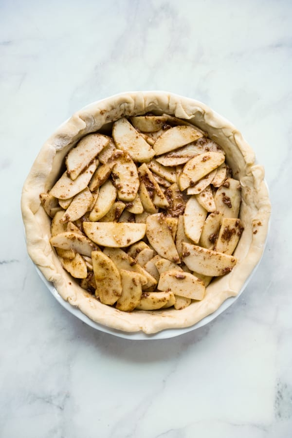 Unbaked apple pie filled with sliced apples