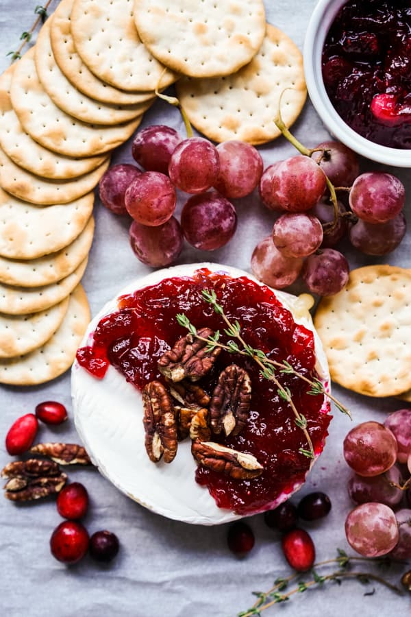 Top down view of Baked brie topped with cranberry sauce, surrounded by crackers and grapes