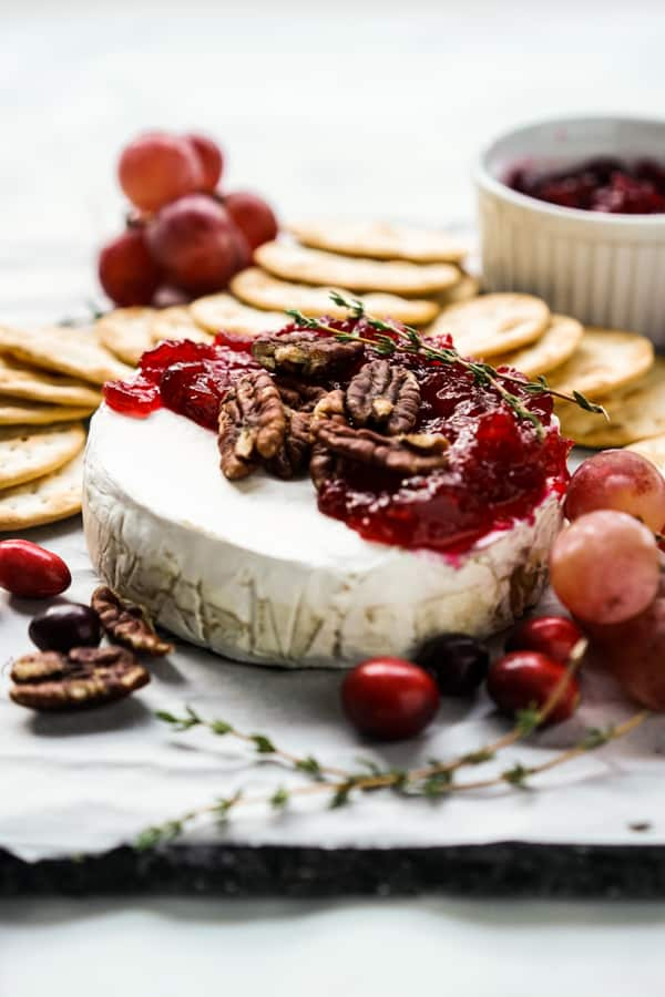 Cranberry Baked Brie with crackers and a small bowl of cranberry sauce and crackers in the background