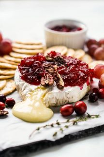 A platter with melted cheese oozing out of baked brie, topped with cranberries and pecans, with crackers surrounding the brie