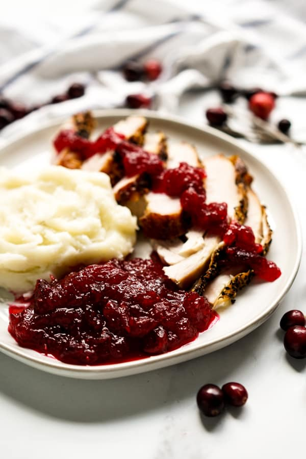 A plate of turkey and mashed potatoes with cranberry sauce