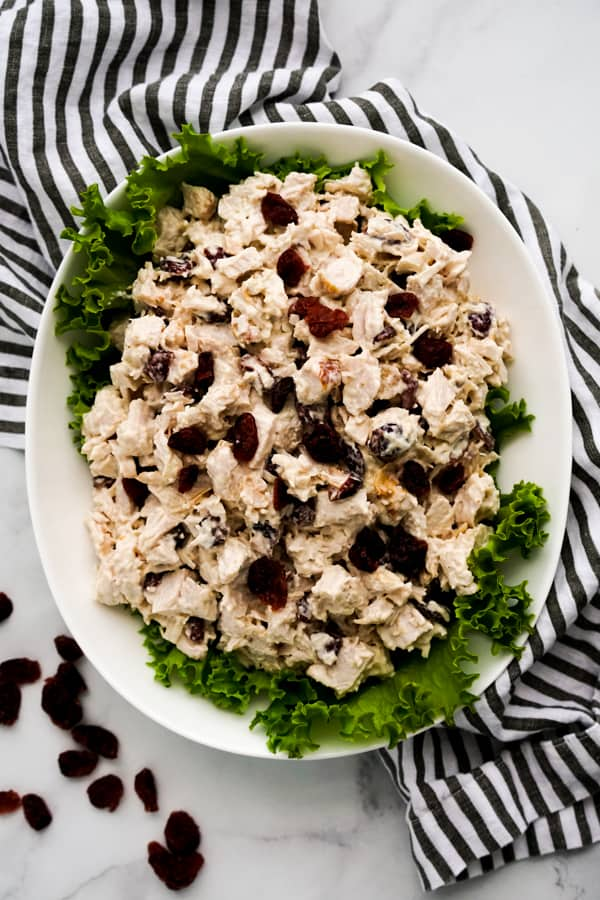 A rectangular plate of turkey salad decorated with green lettuce