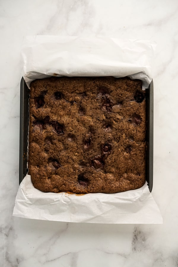 Brownie in baking dish lined with parchment paper after baking