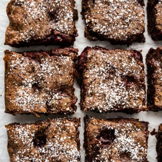 Six square pieces of chocolate brownies loaded with cherries, topped with powdered sugar