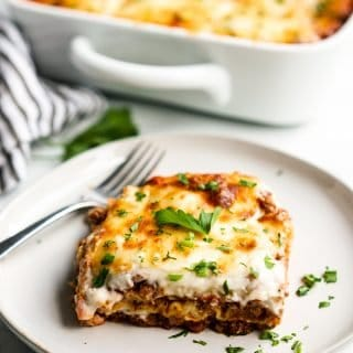 A slice of lasagna with a fork on a plate with a casserole behind it
