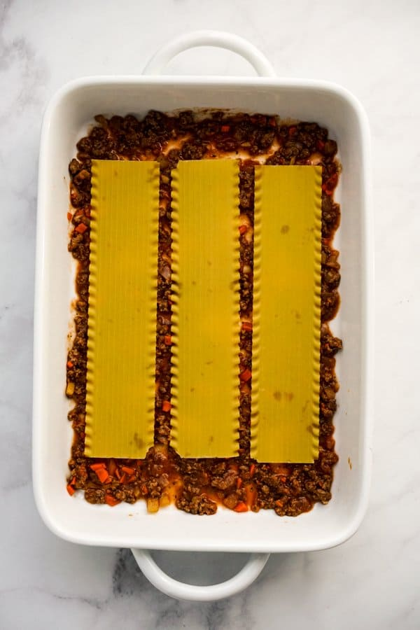 Lasagna noodles on top of bolognese sauce in casserole dish