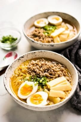 Two bowls of ramen noodles with boiled eggs, bamboo shoots and pork.