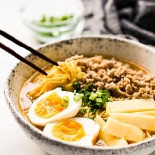 Chopsticks sticking into a bowl of noodles