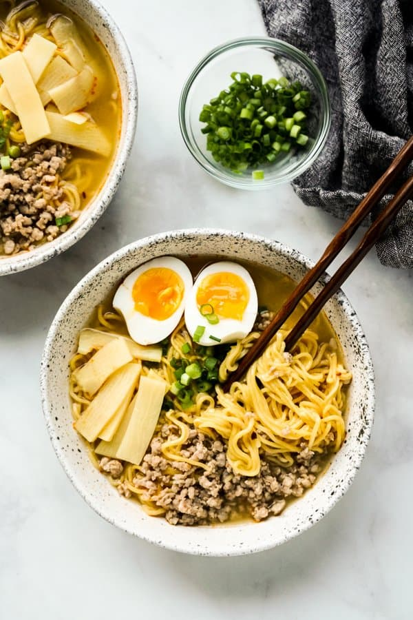 Top down view of a bowl of noodle soup with chopsticks in it