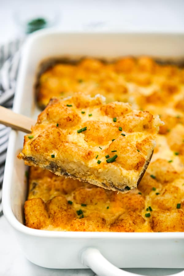 Lifting up tater tot breakfast bake out of the casserole dish